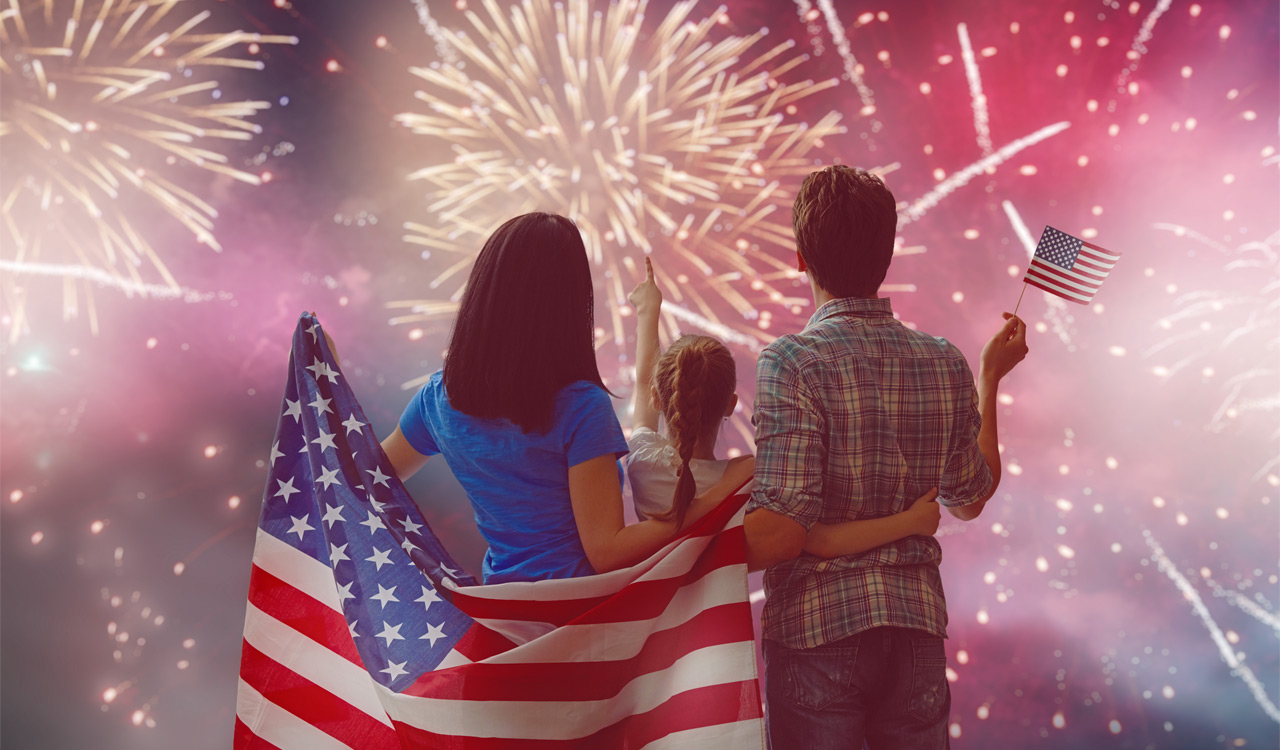 Family with USA flag watching fireworks safely